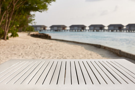 Empty top of white wooden table for product placement and display. Blue lagoon with water bungalows and tropical plants on background. Maldives
