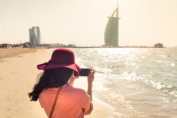 Girl taking picture at a famous beach in Dubai