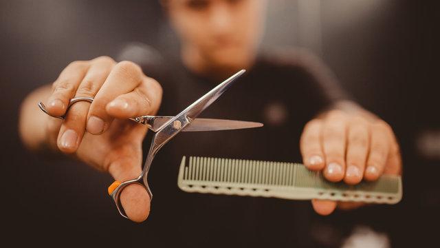Barber shop. Close-up of barber holds clip-on hair clipper barbershop