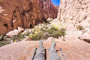 Fototapete - Tourist traveler feet legs resting rock cliff canyon.