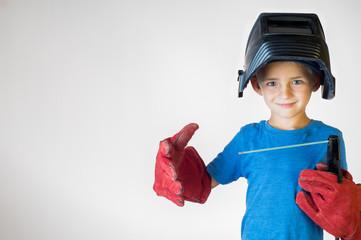 Happy little kid in welder mask and welding equipment.