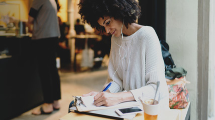 Intelligent international student female wearing stylish clothes writing ideas for the diploma work while sitting in a modern city coffee shop on a weekend day. Freelancer analyzing market data.