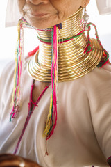 Long Neck woman weaving traditional thai fabric, in Bangkok, Thailand