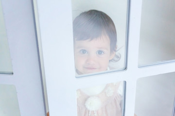 Baby girl smiles in a room near the window