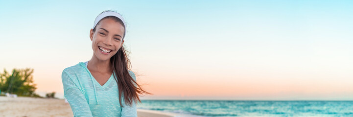 Happy healthy Asian girl smiling at beach sunset banner landscape. Lovely chinese caucasian mixed race fit model face portrait.