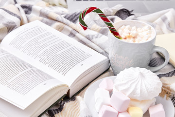 Winter mood composition Christmas Day at home with cup of hot cacao or coffee with marshmallow sweets candy cane and lollipop Santa Claus read book in the bed with wool knitted plaid New Year.