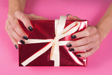Female hand with black nails manicure on red gift box with white bow on pink background, close up