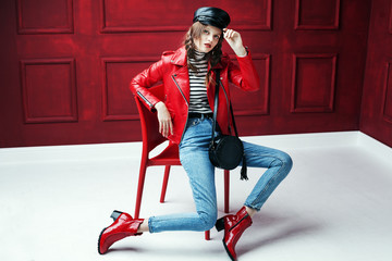 Full body studio fashion portrait of young beautiful woman posing on chair. Model wearing stylish leather cap, biker jacket, stripped turtleneck, blue jeans and red textured ankle boots.