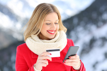 Woman paying with credit card and phone in winter