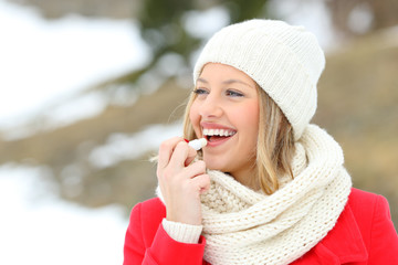 Girl protecting lips with lip balm in winter
