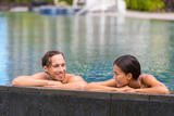 Happy swimming pool couple having fun laughing talking on for Health spa vacations for couples