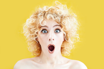 Surprised curly blonde girl with excited face looking at the camera with mouth open against yellow background