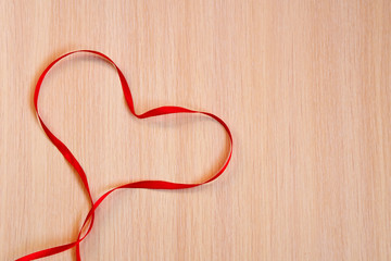 Red Ribbon Heart on a wooden background. Valentines Day concept