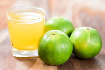 Green tangerine orange fruit and juice on wooden background, healthy food