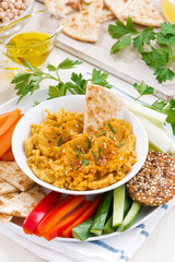 Arabic sauce hummus with fresh vegetables and pita bread, top view, vertical