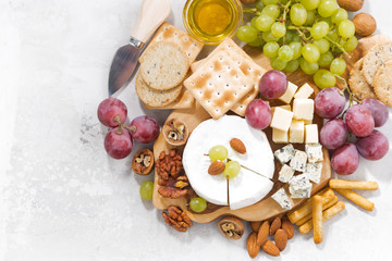 camembert, grapes and snacks on a white table, top view