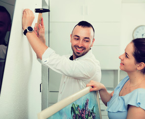 Female and her husband are hanging picture together