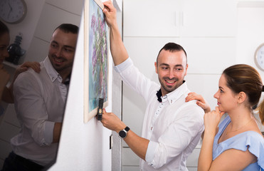 Couple is doing repair and hanging picture on the wall