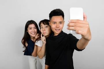 Group Of Three Young Asian Woman Indoors Against White Background Using Mobile Phone While Taking Selfie Picture