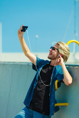 Blonde man outside taking selfie with smartphone