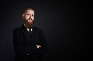 businessman with beard on black background in black suit place for copy-paste
