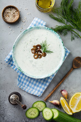 Traditional Greek sauce Tzatziki. Yoghurt, cucumber, dill, garlic and salt oil in a ceramic bowl on a gray stone or concrete background. Rustic style. Selective focus. Top view.
