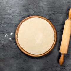 Fototapete - Pizza dough on round wooden board with rolling pin