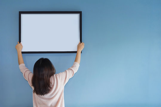Asian woman holding a picture frame on blue wall.