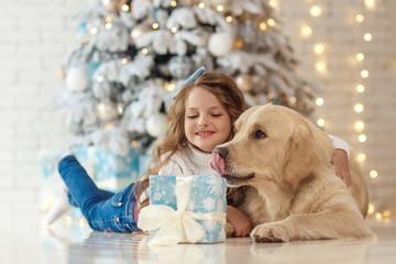 Little cute girl with a golden retriever dog near christmas tree