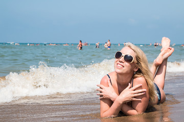 Blond woman on the beach in a water of the sea