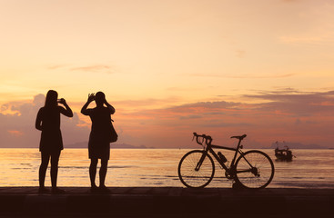 Silhouette bicycle and people take photo at beach sunset background