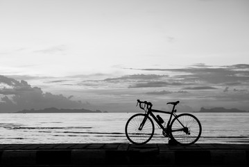 Silhouette bicycle on the beach sunset background,black and white tone
