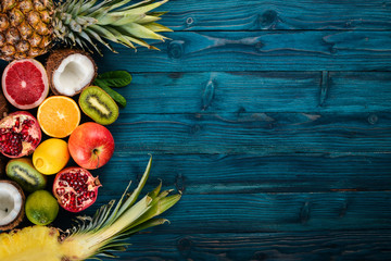 Fresh Tropical Fruits. Pineapple, coconut, kiwi, orange, pomegranate, grapefruit. On a wooden background. Top view. Free space for text. Wall mural