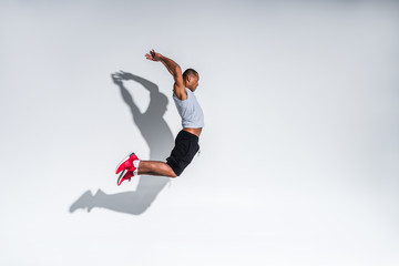 side view of young african american sportsman jumping on grey Wall mural