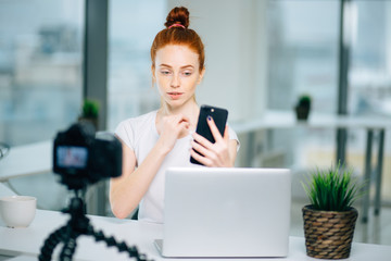 Young female redhead blogger with laptop recording video at home and take selfie