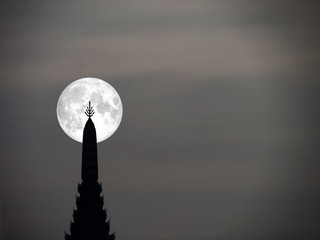 super moon in night sky and silhouette top of ancient pagoda
