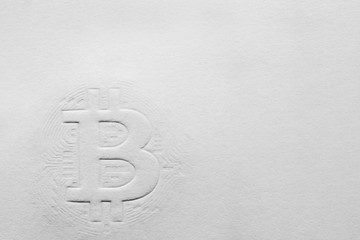 relief sign of bitcoin on a paper background. copy space