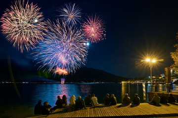 Crowd watching fireworks and celebrating. Beautiful firework display for celebration on the Garda Lake,italy,Brightly Colorful Fireworks