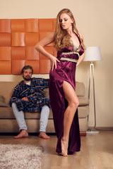 Image of dancing blonde in long negligee and men in dressing gown