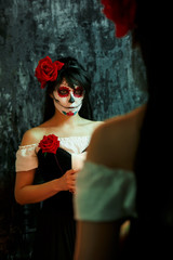 Halloween photo of woman with makeup on face with red flowers