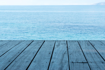 View from empty wooden deck table to  blue sea background