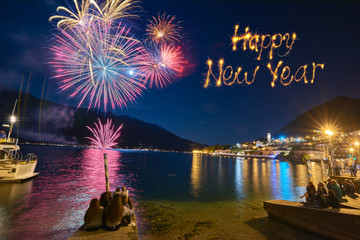 Happy new year  written with  firework on firework background.Beautiful firework display for celebration on the Grda Lake,italy,Brightly Colorful Fireworks