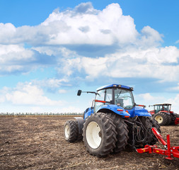 Fototapete - Agricultural machinery cultivates the field