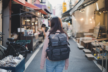 Back side of Asian woman with backpack travelling in market shopping landmark in old city on holiday