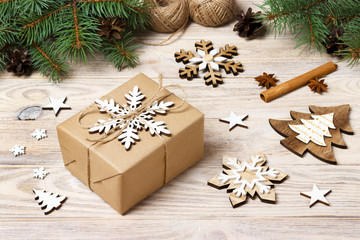 Christmas background with gift boxes wrapped in kraft paper, fir tree branches, pine cones, cinnamon sticks and stars anise on white wooden background
