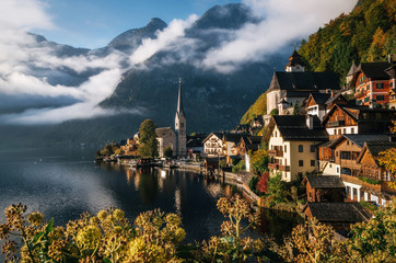 Scenic view of famous Hallstatt lakeside town reflecting in Hallstattersee lake in the Austrian Alps in morning light in autumn with bushes and flowers on the foreground, Salzkammergut region, Austria