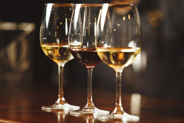Glasses of white and red wine on bar counter