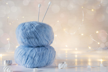Two blue fluffy ball yarn and knitting needles. Christmas background.