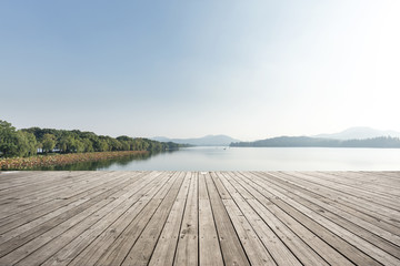 empty wooden floor with beautiful lake in blue sky