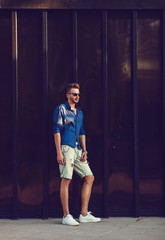 handsome fashion man wearing sunglasses and posing near wall